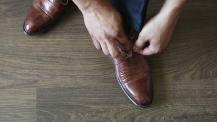 The man puts shoes on.