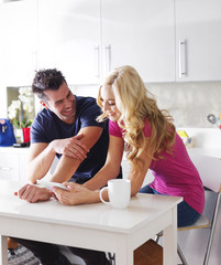 couple using tablet device in kitchen together