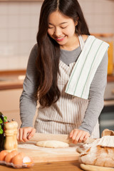 asian young woman is baking bread in her home kitchen