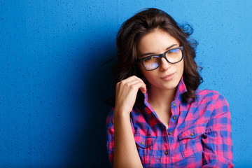 Portrait attractive woman in glasses  on blue background.