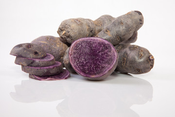 Sliced and whole Vitelotte potatoes