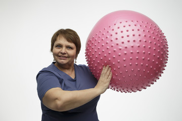 Mature woman doing exercises with pink ball in the studio
