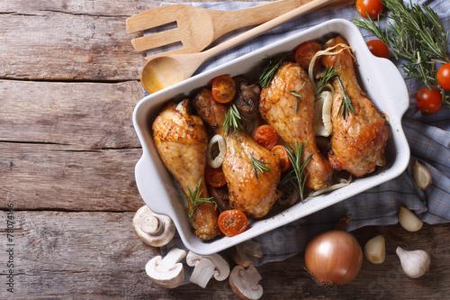Fototapeta Baked chicken legs with mushrooms. horizontal top view