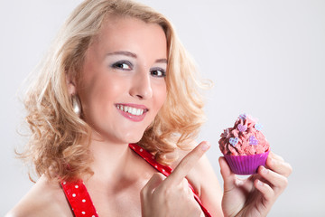 Junge hübsche Frau zeigt frischen Cupcake