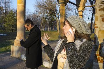 Girl talking on the phone while her boyfriend waits