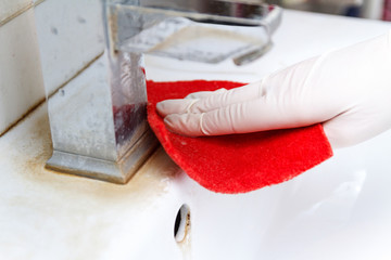 Hand in glove cleans dirty washbasin red sponge