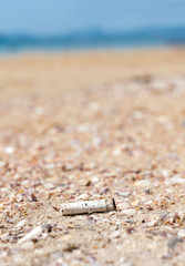 Cigarette butt discarded left on beach, concept photo.