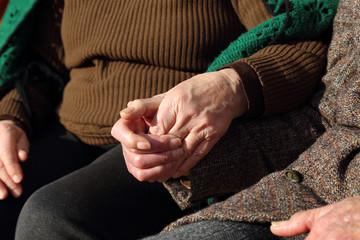Coppia di anziani che si tengono per mano in segno d'amore