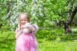 Adorable little girl in blossoming apple tree garden