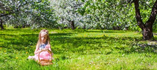 Adorable little girl have fun in blossoming apple tree garden at