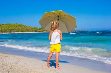 Little adorable girl with big yellow umbrella on tropical beach