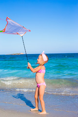 Little happy girl playing with flying kite during tropical beach