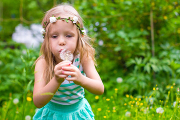 Adorable little girl blowing a dandelion in the garden