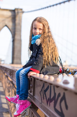 Adorable little girl sitting at Brooklyn Bridge