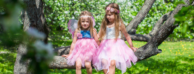 Little adorable girls sitting on blossoming tree in apple garden