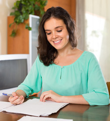 Brunette woman filling papers at home
