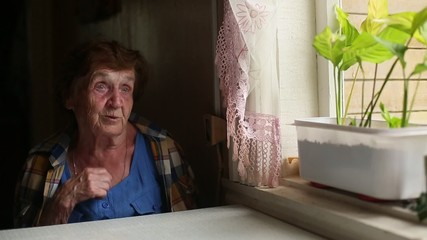Old lonely woman sitting near the window in his house. (HD)