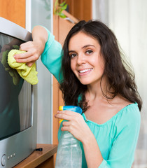 Brunette woman cleaning TV