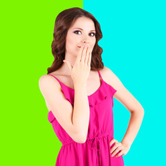 Beautiful young girl in dress on colorful background