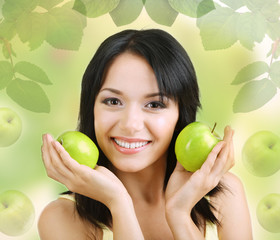 Beautiful young woman with green apple on natural background