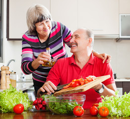 happy  elderly couple cooking with tomatoes