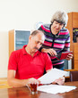 serious mature man with wife reading financial documents