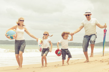 Happy family dancing on the beach at the day time.