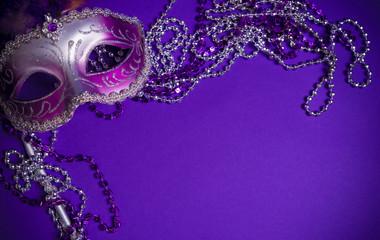 Purple Mardi-Gras or Venetian mask on purple background