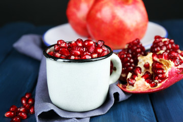 Juicy ripe pomegranate on wooden table, on dark background