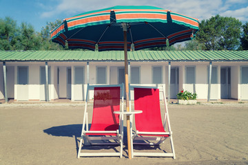 vintage beach chair, ubrella and hut.