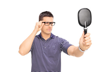 Man with glasses looking himself in a mirror