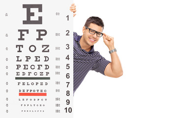 Man with glasses posing behind an eyesight test
