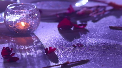 candle burns in the transparent wine glass among rose petals