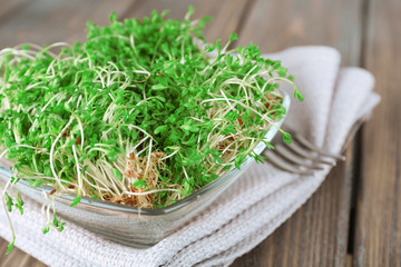 Fresh cress salad in glass bowl with napkin and wooden planks