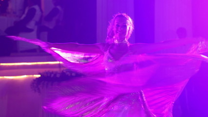 blonde girl in theatrical costume with wings dances and turns