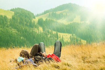 Couple lying in on the hills with beautiful mountains