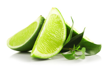 Juicy slices of lime with green leaves isolated on white