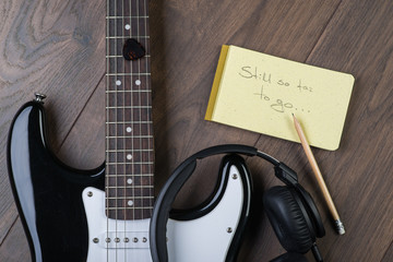 Black and white electric guitar on the wooden floor with notepad
