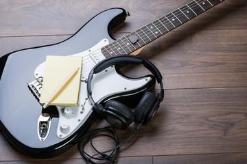 Black electric guitar with notepad, headphones and pencil