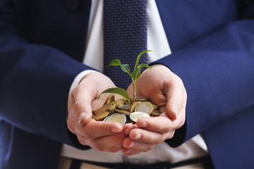 Handful of coins with growing sprout, closeup view