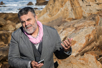 Attractive bearded man on the coast talking on phone