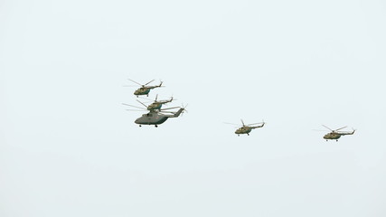 Helicopters are flying in the sky during military parade.