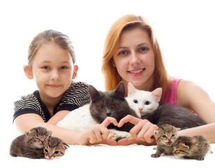 girls hugging cats