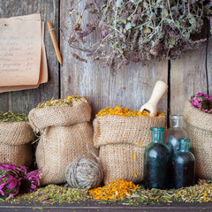 Healing herbs in hessian bags, bottles of tincture and paper she