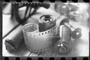 Old film stylized photo of rolled up film, cassette and retro ca