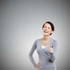 Cheerful girl gives thumb up, isolated on grey