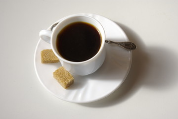 Cup of coffee and cubes brown sugar