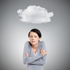 Young girl feels cold, isolated on grey background with cloud