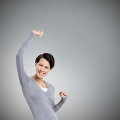 Beautiful girl gestures triumphal fists, isolated