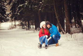 Happy couple in winter forest sitting on a sled